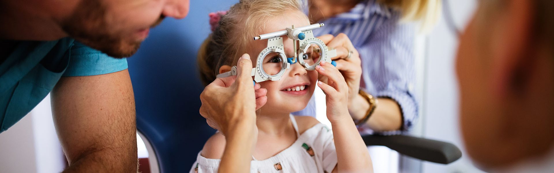 Ophthalmologist is checking the eye vision of little cute girl in modern clinic. Family with daughter in ophthalmology clinic.